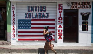 """In this April 3, 2020 photo, a woman carrying a child walks past a closed courier business featuring a U.S. flag and the Spanish phrase: """"Send to U.S.A"""" in the largely indigenous town of Joyabaj, Guatemala, where half of the residents depend on remittances, almost all from the U.S. The devastation wrought by COVID-19 across the developed world is cutting into the financial lifelines for people across Latin America, Africa and Asia. (AP Photo/Moises Castillo)"""