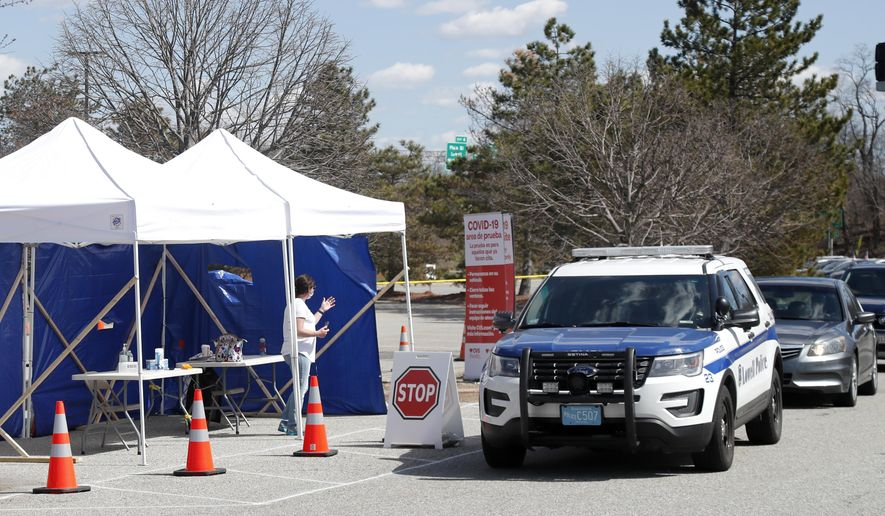 Cars line up with people seeking COVID-19 tests, Tuesday, April 7, 2020, in Lowell, Mass. The City of Lowell, the state and CVS Health have teamed up to open Massachusetts' first free, rapid COVID-19 drive-up testing site that will be able to test up to 1,000 people per day and provide results in about 15 minutes. (AP Photo/Elise Amendola)