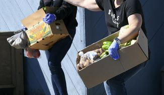 Dolly Sherman, right, prepares to place produce in the trunk of a car during the Conneaut Human Resources Center's monthly produce distribution on on Monday April 6, 2020, morning in Conneaut, Ohio. (Warren Dillaway/The Star-Beacon via AP)