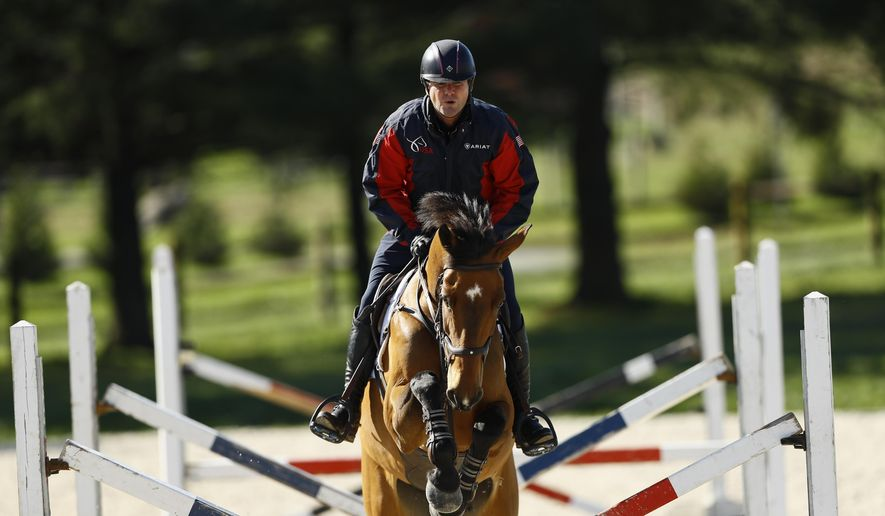 Phillip Dutton, a medal-winning equestrian on the U.S. Olympic team, rides Z, through a series of jumps while training at his farm, Thursday, April 2, 2020, in West Grove, Pa. (AP Photo/Matt Slocum)