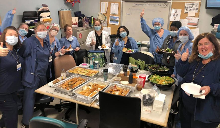 In this March 26, 2020 photo provided by Maureen Morin and Federico's Pizza, staff members of the Hackensack Meridian Jersey Shore University Medical Center give a thumbs-up in Neptune City, N.J., as they eat a donated meal from the Belmar, New Jersey pizzeria. With restaurants closed for all but takeout orders during the coronavirus outbreak, the owners of the pizzeria could have shut down and laid off their 20 employees. Instead, the business's owners took out a $50,000 line of credit and guaranteed their workers they'll stay on the payroll for at least two months. (Courtesy of Maureen Morin via AP)