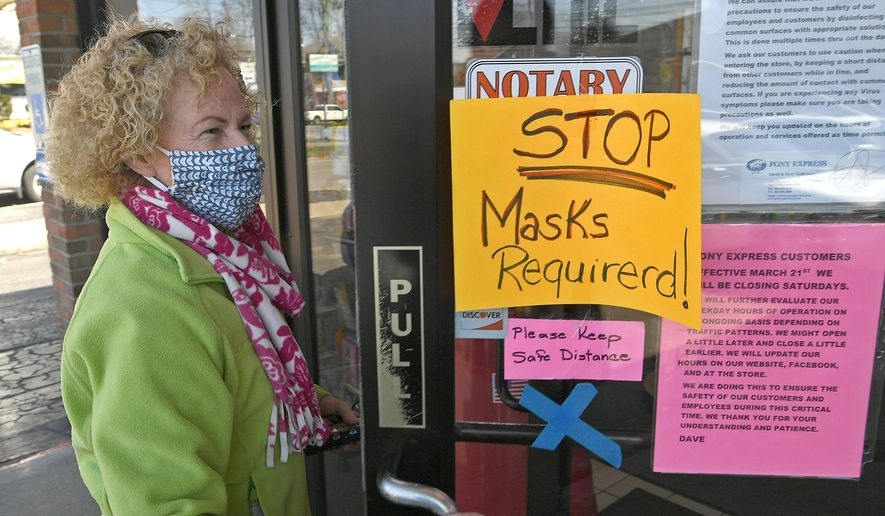 Bridget Niemic, of Millcreek Township, Erie County, Pennsylvania, enters the Pony Express shipping, postage and delivery store, 1903 W. Eighth St., in Erie, Pennsylvania on Monday, April 6, 2020. The store has implemented a mandatory face mask policy for patrons. (Christopher Millette/Erie Times-News via AP)