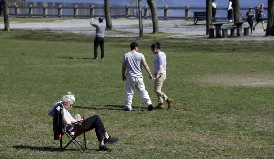 People read and walk through India Point Park, in Providence, R.I., as temperatures reach the 60s, Monday, April 6, 2020. Many people are working from home out of concern for the coronavirus. The new coronavirus causes mild or moderate symptoms for most people, but for some, especially older adults and people with existing health problems, it can cause more severe illness or death. (AP Photo/Steven Senne)