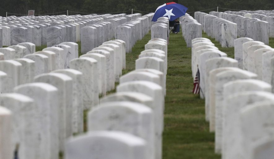 A visitor sits at a gravesite at Fort Sam Houston National Cemetery in San Antonio, Tuesday, April 7, 2020. National cemeteries are open and will continue to provide interments for veterans and eligible individuals, but due to the COVID-19 coronavirus outbreak committal services and the rendering of military funeral honors have been discontinued until further notice. (AP Photo/Eric Gay) ** FILE **