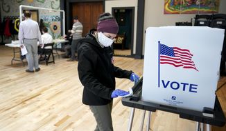 Shanon Hankin, cleans a voter booth after it was used for voting at the Wil-Mar Neighborhood Center Tuesday,  April 7, 2020 in Madison, Wis.  Voters across the state are ignoring a stay-at-home order in the midst of a pandemic to participate in the state's presidential primary election. (Steve Apps/Wisconsin State Journal via AP)