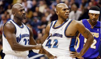 Washington Wizards' Jerry Stackhouse, center, is restrained by teammate Michael Jordan after being called for a first-quarter foul as Los Angeles Lakers' Samaki Walker stands at right Friday, Nov. 8, 2002, in Washington. (AP Photo/Ken Lambert) **FILE**
