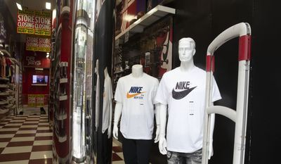 In this Thursday, March 19, 2020 photo, Nike apparel is shown in a sporting goods store in the Brooklyn borough of New York. The store remains open but signs indicate that it is scheduled to close. (AP Photo/Mark Lennihan)
