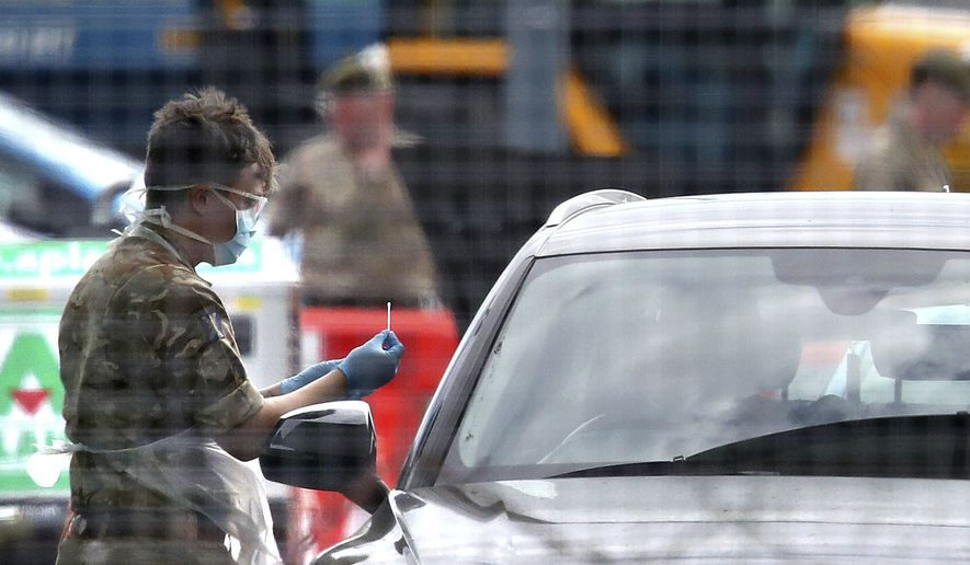 Military Personnel carry out virus testing at a testing facility in the long stay car park at Glasgow Airport as the U.K. continues its lockdown to help curb the spread of the coronavirus, in Glasgow, Scotland, Wednesday, April 8, 2020. The highly contagious COVID-19 coronavirus has impacted on nations around the globe, many imposing self-isolation and exercising social distancing when people move from their homes. (Andrew Milligan/PA via AP)
