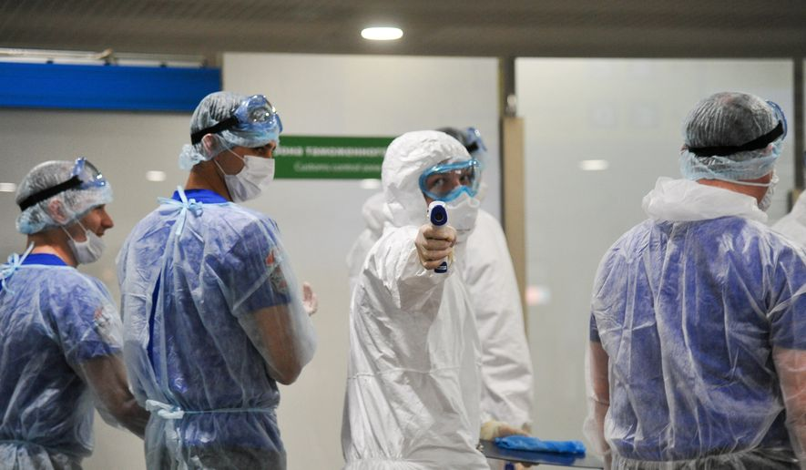 Medical staffers, wearing special suits to protect against coronavirus, one of them with a thermometer, walk inside Sheremetyevo international airport outside Moscow, Russia, Wednesday, March 25, 2020. The new coronavirus causes mild or moderate symptoms for most people, but for some, especially older adults and people with existing health problems, it can cause more severe illness or death. (Aleksandr Avilov, Moscow News Agency photo via AP)