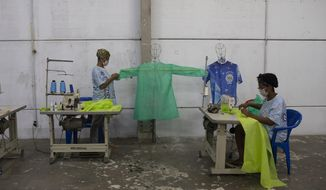 Workers from the Vila Isabel samba school make scrubs, for medical workers to wear during the new coronavirus pandemic in Rio de Janeiro, Brazil, Tuesday, April 7, 2020. Samba schools that a spend all year making Carnival costumes have turned their sewing machines to a different purpose, making scrubs and face masks for medical workers. (AP Photo/Silvia Izquierdo)