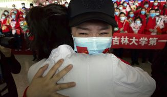 A medical worker from China's Jilin Province reacts as she prepares to return home at Wuhan Tianhe International Airport in Wuhan in central China's Hubei Province, Wednesday, April 8, 2020. Within hours of China lifting an 11-week lockdown on the central city of Wuhan early Wednesday, tens of thousands people had left the city by train and plane alone, according to local media reports. (AP Photo/Ng Han Guan)