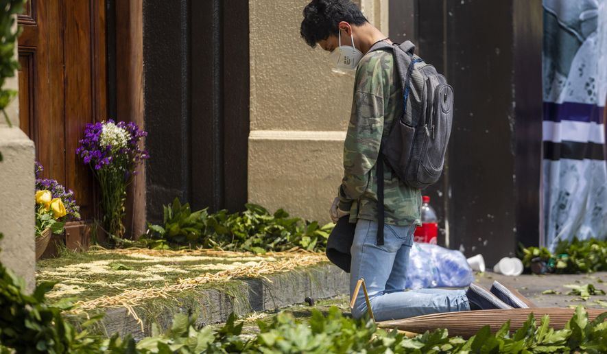 A young man, wearing a mask to protect himself from the spread of the new coronavirus, prays in front of the closed Candelaria church in Guatemala City, Wednesday, April 8, 2020. Catholics prepare to celebrate Holy Week amid measures to prevent the spread of the new coronavirus, including cancelling all religious activities across the country. (AP Photo/Moises Castillo)