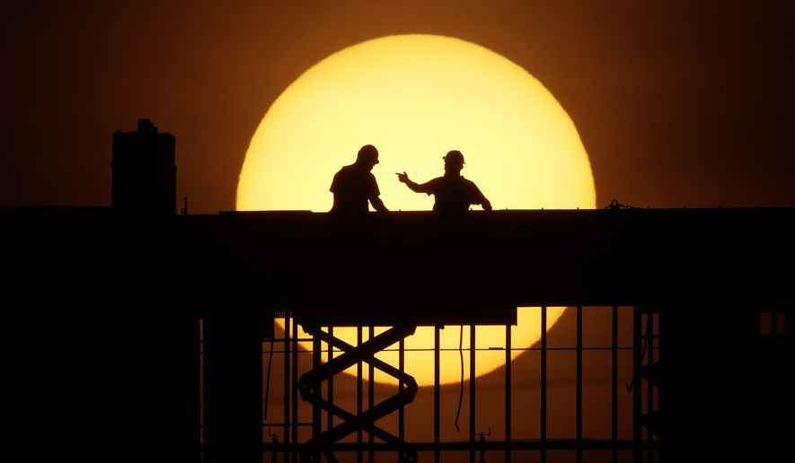 Workers are silhouetted against the rising sun as they toil on a new apartment building in Kansas City, Mo. Wednesday, April 8, 2020. Construction workers are among the people exempt from the city's stay-at-home order which remains in effect in an effort to slow the spread of the new coronavirus. (AP Photo/Charlie Riedel)