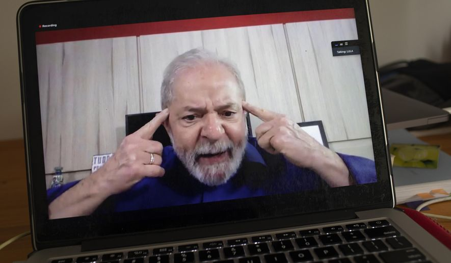 Brazil's former President Luiz Inacio Lula da Silva speaks from his home in Sao Paulo during an interview with The Associated Press via a cloud-based video conferencing service, as seen from a laptop in Rio de Janeiro, Brazil, Wednesday, April 8, 2020. (AP Photo/Silvia Izquierdo)