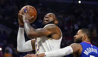 In this March 8, 2020, file photo, Los Angeles Lakers forward LeBron James, left, shoots as Los Angeles Clippers forward Marcus Morris Sr. defends during the second half of an NBA basketball game in Los Angeles. LeBron James says he probably won't feel any closure on the Los Angeles Lakers' remarkable season unless the NBA is able to finish its season. (AP Photo/Mark J. Terrill, File)  **FILE**