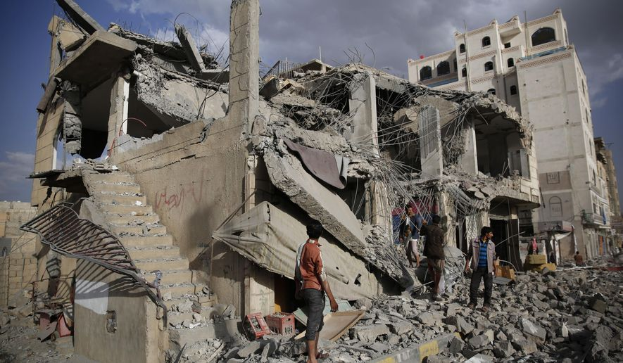 FILE - In this Monday, Jan. 25, 2016 photo, men inspect a house destroyed by a Saudi-led airstrike in Sanaa, Yemen. The missile fired by the Saudi-led coalition killed a judge and his entire family in the Nahda neighborhood, security officials said. The judge was a known Houthi supporter. On Wednesday, April 8, 2020, the Saudi-led coalition fighting the Iranian-backed Houthi rebels in Yemen announced that its forces would begin a cease-fire starting at midnight, in what could pave the way for the first direct peace talks between the two sides that have been at war for more than five years. (AP Photo/Hani Mohammed)