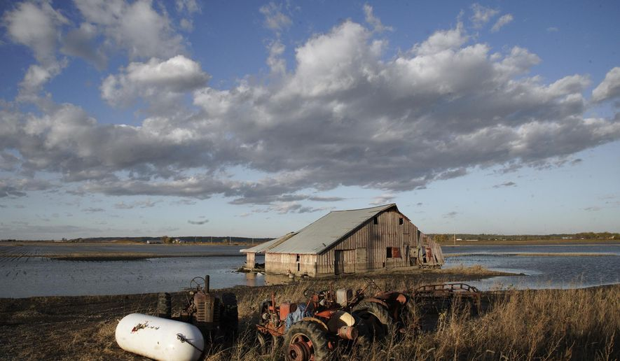 FILE - In this Oct. 22, 2019 photo, a barn sits in floodwaters in Pacific Junction, Iowa. Flooding remains a concern in several states along the Missouri River even though the weather has been kind so far this spring. The flood risk remains high in eastern South Dakota, eastern North Dakota, eastern Nebraska, western Iowa, eastern Kansas and Missouri because the soil remains wet, but the lack of rain and warm temperatures this spring allowed snow to melt gradually across the Plains without worsening the risk. (AP Photo/Nati Harnik File)