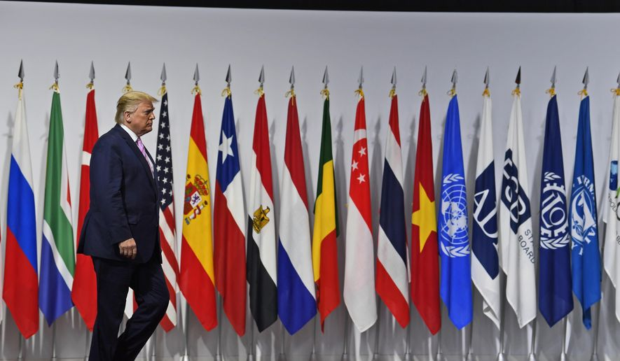 In this June 28, 2019, photo President Donald Trump arrives to greet Japanese Prime Minister Shinzo Abe at the G-20 summit in Osaka, Japan. (AP Photo/Susan Walsh) **FILE**