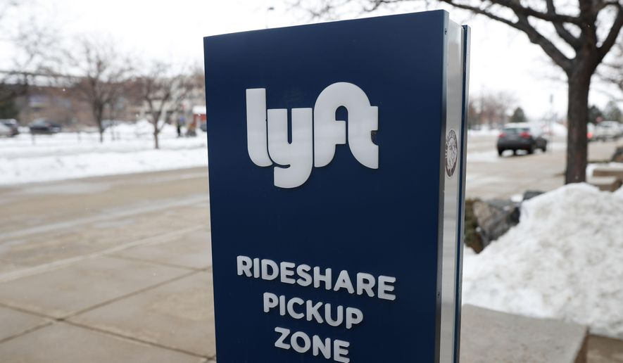 In this  Feb. 12, 2020, photograph, a sign for the car-sharing service Lyft stands near a pickup zone outside the Pepsi Center in downtown Denver. (AP Photo/David Zalubowski, File)