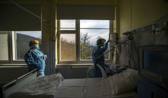 In this March 24, 2020, file photo, medical staff members check a ventilator in protective suits at the care unit for the new COVID-19 infected patients inside the Koranyi National Institute of Pulmonology in Budapest. As health officials around the world push to get more ventilators to treat coronavirus patients, some doctors are moving away from using the breathing machines when they can. (Zoltan Balogh/MTI via AP, File)