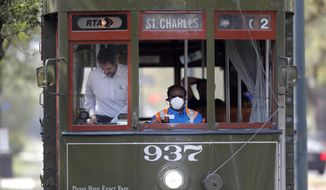 FILE - In this March 19, 2020 file photo, a streetcar conductor wears a mask due to the coronavirus pandemic as she runs her route on St. Charles Ave. in New Orleans. Where political divides marred early recovery efforts after Hurricane Katrina in 2005, Louisiana is showing rare political unity in the fight against the new coronavirus.  (AP Photo/Gerald Herbert, File)