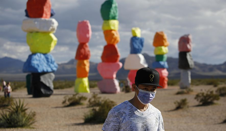 A man wears a mask on his face while visiting the artwork titled Seven Magic Mountains by artist Ugo Rondinone amidst the coronavirus outbreak, Tuesday, April 7, 2020, near Jean, Nev., south of Las Vegas. (AP Photo/John Locher)