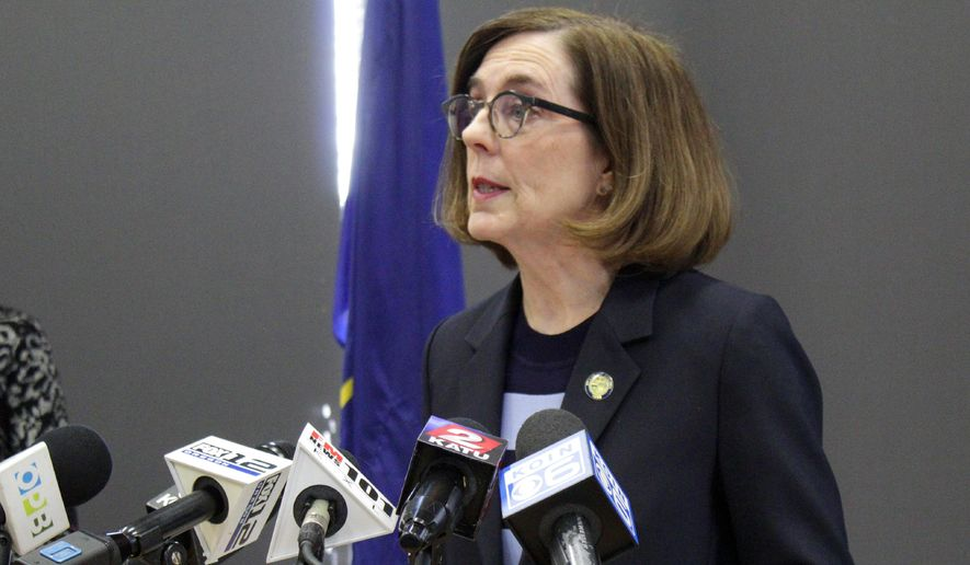 FILE - In this March 16, 2020, file photo, Gov. Kate Brown speaks at a news conference to announce a four-week ban on eat-in dining at bars and restaurants throughout the state in Portland, Ore., to slow the spread of the new coronavirus. Brown said Wednesday, April 8, 2020, that Oregon's K-12 schools will remain closed though the end of the academic year due to the coronavirus outbreak, placing the state's more than 550,000 students and their teachers in uncharted territory as districts with vastly different resources plan for weeks of remote learning. (AP Photo/Gillian Flaccus, File)