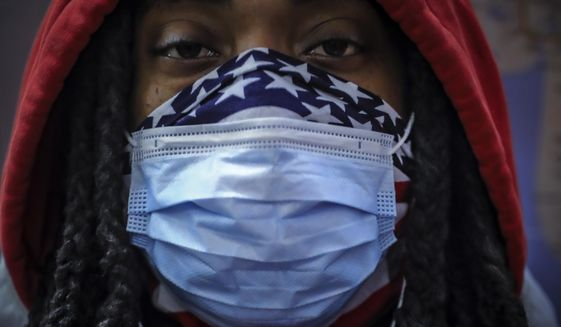 In this April 7, 2020, photo, a subway rider wears a mask and a bandana to protect himself against COVID-19 in New York. As the coronavirus tightened its grip across the country, it is cutting a particularly devastating swath through an already vulnerable population, black Americans. (AP Photo/Bebeto Matthews)