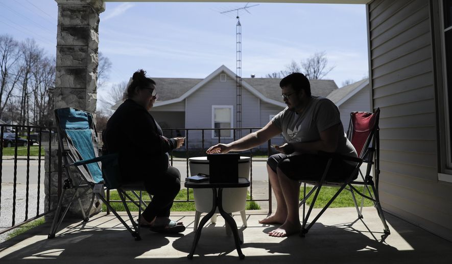 Amanda Burkhead and Josh Cupit play a card game while sitting on the front porch, Thursday, April 2, 2020, in Greensburg, Ind. The couple worked at Honda will the plant was shut down due to COVID-19. Three southeast Indiana counties have among the highest per-capita coronavirus infection rates in the country.  (AP Photo/Darron Cummings)