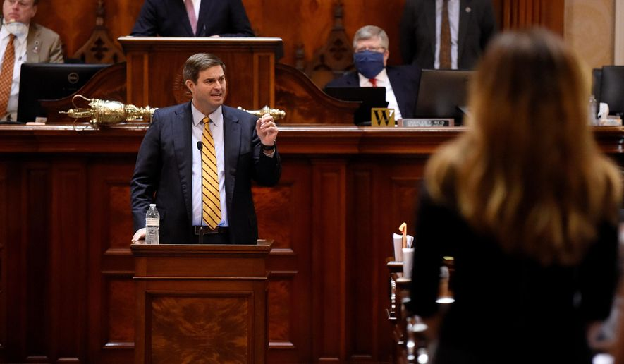 House Ways and Means Committee Chairman Murrell Smith, center, answers a question from state Rep. Nancy Mace, right, on the House floor during a special, one-day session of the South Carolina Legislature on Wednesday, April 8, 2020, in Columbia, S.C. This year's session has been paused for several weeks amid the new coronavirus outbreak. (AP Photo/Meg Kinnard)