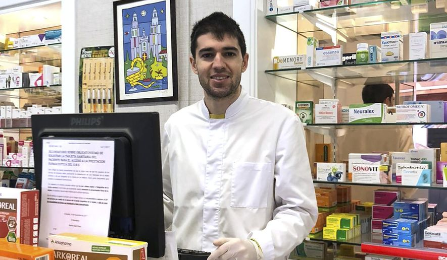 In this photo taken on March 18, 2020, soccer player Toni Dovale poses while working in his family pharmacy in A Coruna, Spain. Dovale, a former Sporting Kansas City and Celta Vigo player who came through Barcelona's famed youth academy, is back at work in his home country while soccer competitions remain on hold because of the COVID-19 virus. Dovale is making calls to try to guarantee there are enough protective masks, gloves and other medical supplies that can help slow the spread of the virus in hard-hit Spain.  The COVID-19 coronavirus causes mild or moderate symptoms for most people, but for some, especially older adults and people with existing health problems, it can cause more severe illness or death. (Photo via AP)