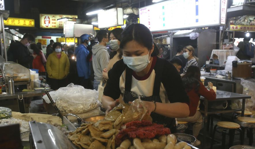 A vendor wears face mask to help curb the spread of the coronavirus and waits for customers at a night market in Taipei, Taiwan, Wednesday, April 8, 2020. The new coronavirus causes mild or moderate symptoms for most people, but for some, especially older adults and people with existing health problems, it can cause more severe illness or death. (AP Photo/Chiang Ying-ying)