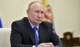Russian President Vladimir Putin attends a meeting of the military technical cooperation with foreign countries via video conference at the Novo-Ogaryovo residence outside Moscow, Russia, Thursday, April 9, 2020. (Alexei Druzhinin, Sputnik, Kremlin Pool Photo via AP)
