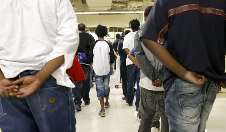 In this June 26, 2014, file photo, inmates at the Cook County jail head off to bond court after their arrest the night before in Chicago. A federal judge has ordered Cook County Jail to take steps to protect inmates from the coronavirus. (AP Photo/Charles Rex Arbogast File)