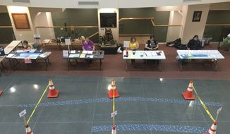 FILE - In this April 7, 2020, file photo poll workers used caution tape and pylons to set up aisles to help maintain proper social distancing at a polling place set up at the Government Center in Superior, Wis., as voters, ignoring a stay-at-home order over the coronavirus threat, cast ballots in the state's presidential primary election.  A partisan fight over voting in Wisconsin was the first issue linked to the coronavirus to make it to the Supreme Court. (Dan Kraker/Minnesota Public Radio via AP, File)