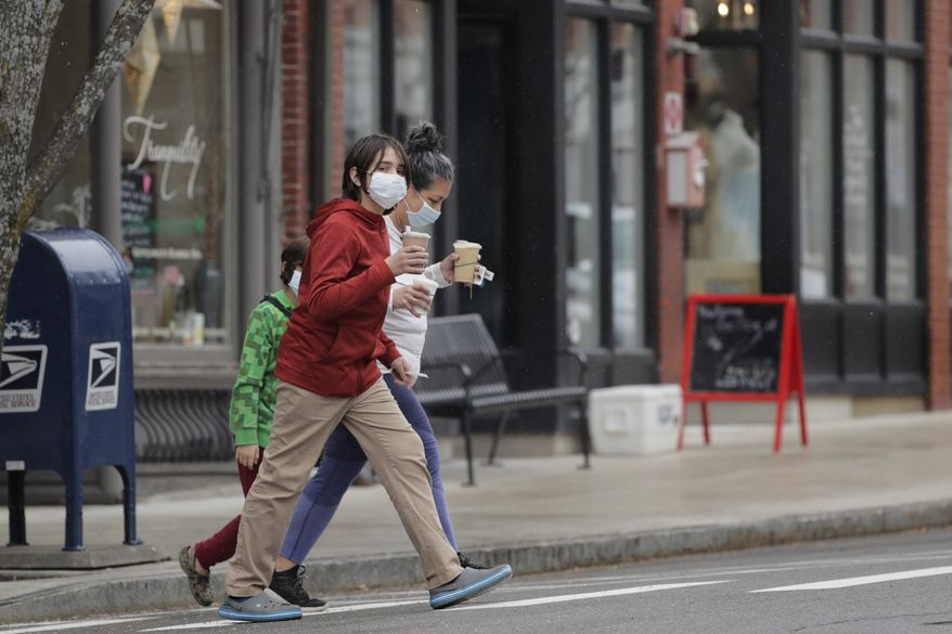A family, wearing masks due to the virus outbreak, carry drinks as they walk through the empty streets of the village of Exeter, N.H., Thursday, April 9, 2020. (AP Photo/Charles Krupa)