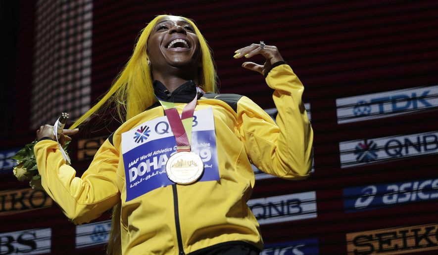 FILE - In this file photo dated Monday, Sept. 30, 2019, Shelly-Ann Fraser-Pryce of Jamaica, gold medalist in the women's 100 meters, reacts during the medal ceremony at the World Athletics Championships in Doha, Qatar.  Moving from their sports field to the living room, many athletes around the world are doing their bit to boost public health during the coronavirus pandemic lockdown, and one of them is two-time 100-meter champion Shelly-Ann Fraser-Pryce of Jamaica, who is reading her children's book. (AP Photo/Nariman El-Mofty, FILE)