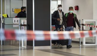 First people from Craiova in Romania arrive with their luggage and face masks at the 'Schoenefeld Airport' in Berlin, Germany, Thursday, April, 2020. The first planes with harvest workers from Romania have been landing in the morning. (Soeren Stache/dpa via AP)