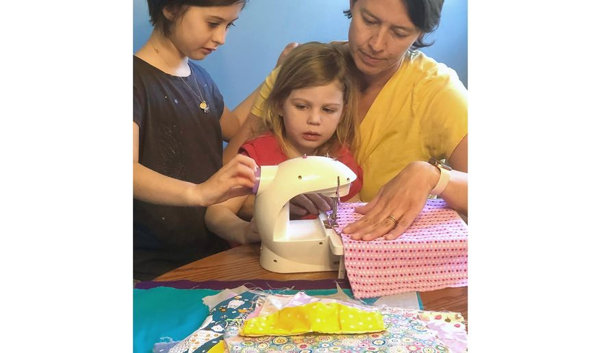 "This April 3, 2020 photo shows Erin Bried, right, with her daughters Ellie, 9, left, and Bea, 4, as they sew masks. Bried is the author of ""How to Sew a Button: And Other Nifty Things Your Grandmother Knew,"" left, and ""How to Build a Fire: And Other Handy Things Your Grandfather Knew,"" (Holly Bemiss via AP)"