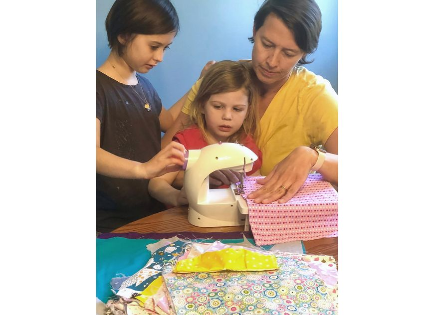 """This April 3, 2020 photo shows Erin Bried, right, with her daughters Ellie, 9, left, and Bea, 4, as they sew masks. Bried is the author of """"How to Sew a Button: And Other Nifty Things Your Grandmother Knew,"""" left, and """"How to Build a Fire: And Other Handy Things Your Grandfather Knew,"""" (Holly Bemiss via AP)"""