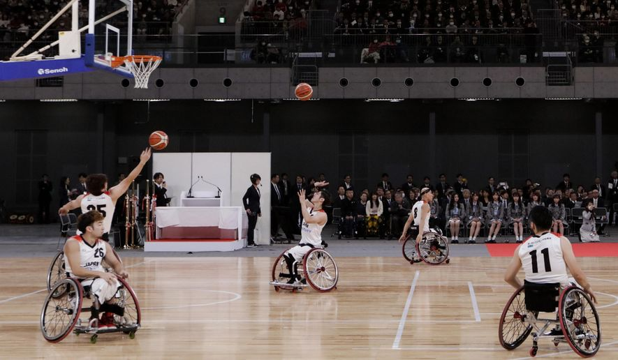 """FILE - In this Feb. 2, 2020, file photo, members of Japan's national wheelchair basketball team warm up on the court during a grand opening ceremony of the Ariake Arena, a venue for volleyball at the Tokyo 2020 Olympics and wheelchair basketball during the Paralympic Games, in Tokyo. The International Paralympic Committee has """"cash flow"""" problems. But its President Andrew Parsons has ruled out going to the International Olympic Committee for help. (AP Photo/Jae C. Hong, File)"""