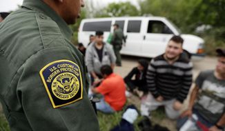 FILE - In this Thursday, March 14, 2019, file photo, a Border Patrol agent talks with a group suspected of having entered the U.S. illegally near McAllen, Texas. The Trump administration has quietly shut down the nation's asylum system for the first time in decades amid coronavirus concerns, largely because holding people in custody is considered too dangerous. (AP Photo/Eric Gay, File)