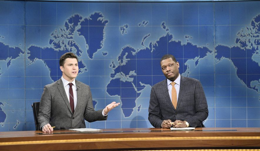 """This Feb. 29, 2020 photo released by NBC shows Colin Jost, left, and Michael Che during the Weekend Update sketch on """"Saturday Night Live"""" in New York. The show will be back on the air this weekend with a show that abides by social distancing rules. NBC says the comedy sketch show will include include a """"Weekend Update"""" news segment and original content from """"SNL"""" cast members. The material will be produced remotely, in compliance with efforts to limit the spread of the coronavirus. (Will Heath/NBC via AP)"""