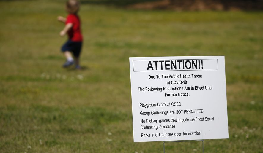 A child plays near a sign advising people that the playground is closed and social distancing is requirements Thursday, April 9, 2020, in Rutledge, Ga. The new coronavirus causes mild or moderate symptoms for most people, but for some, especially older adults and people with existing health problems,  it can cause more severe illness or death. (AP Photo/John Bazemore) **FILE**