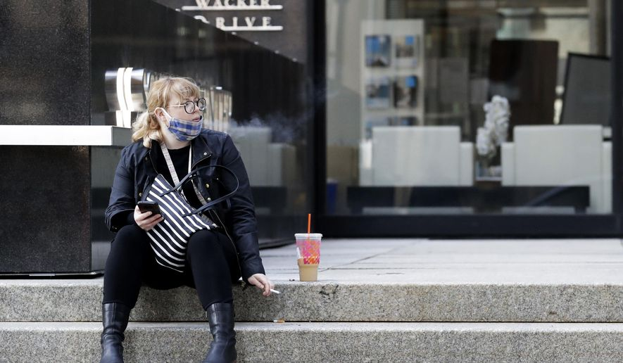 A woman sits as she smokes in downtown Chicago, Wednesday, April 8, 2020. It's gorgeous outside but please behave. No end is in sight for the stay-at-home order as Chicagoans fight summer weather temptations. (AP Photo/Nam Y. Huh)