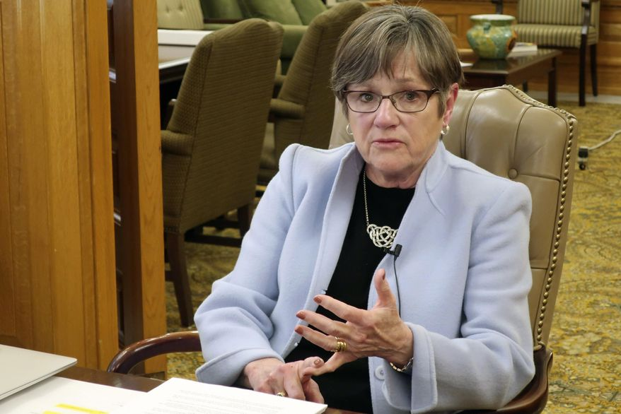 In this March 25, 2020 file photo, Kansas Gov. Laura Kelly answers questions in her office at the Statehouse in Topeka, Kan. Gov. Kelly on Thursday, April, 9, 2020 filed suit after a legislative panel overturned her executive order that was aimed at stopping religious and funeral gatherings of more than 10 people. Kelly has asked the Kansas Supreme Court to expedite the case in hopes of getting clarity by Sunday, which is Easter. (AP Photo/John Hanna File)