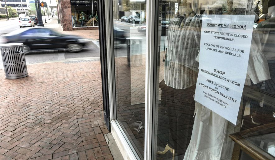A sign is posted on the window of the clothing and furnishings business Byron & Barclay notifying customers of temporary closure of the storefront during the coronavirus pandemic, Wednesday, April 8, 2020, in downtown Owensboro, Ky. (Greg Eans/The Messenger-Inquirer via AP)