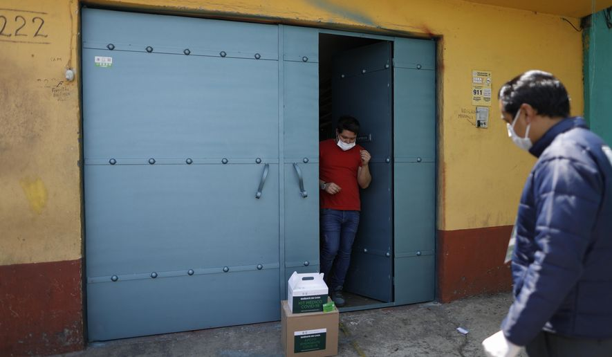 A man whose aunt is suffering from symptoms consistent with COVID-19 receives a delivery of medical and food supplies dropped off by workers from the city government, in the Coyoacan district of Mexico City, Thursday, April 9, 2020. To help halt the spread of the new coronavirus, the Mexican megalopolis is making home deliveries to households with a symptomatic person, providing kits containing food staples, face masks, gloves, antibacterial gel, paracetamol, a thermometer, and benefits cards with a balance of 1000 pesos (around $42). (AP Photo/Rebecca Blackwell)