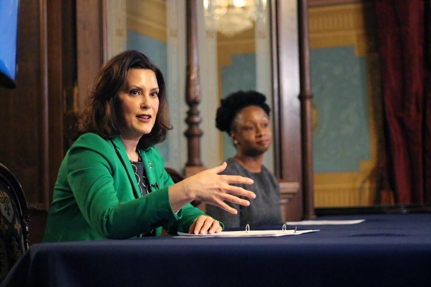"""In a pool photo provided by the Michigan Office of the Governor, Michigan Gov. Gretchen Whitmer addresses the state during a speech in Lansing, Mich., Thursday, April 9, 2020. The governor signed an executive order extending her prior """"Stay Home, Stay Safe"""" order through the end of April. The order limits gatherings and travel and requires all workers who are not necessary to sustain or protect life to stay home. The order also imposes more stringent limitations on stores to reduce foot traffic to slow the spread of the coronavirus. (Michigan Office of the Governor via AP, Pool)"""