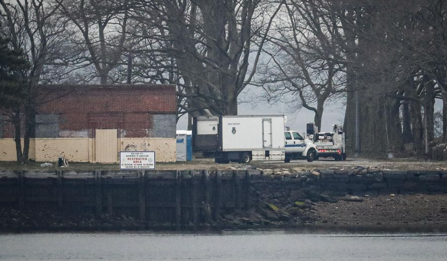 A truck loaded with bodies drives toward a burial trench on Hart Island, Thursday, April 9, 2020, in the Bronx borough of New York. New York City could bury virus victims in temporary graves if city morgues are overwhelmed. (AP Photo/John Minchillo) ** FILE **